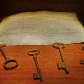 Im Museum ein altes Schriftstück und Schlüssel.